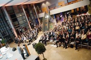 Blick über einen gut gefüllten Saal: Michael Söndermann vom Büro für Kulturwirtschaftsförderung Köln spricht zu den Gästen der Veranstaltung. Foto: Mario Zgoll