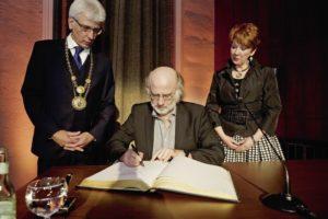 Preisträger Frank Schulz trägt sich ins  Goldene Buch der Stadt Kassel ein. Foto: Mario Zgoll