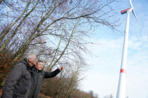 Klaus Becker und Oliver Penner (v.l.) vom Aktionsbündnis Märchenland an einem Windrad, wie es bald auch im Reinhardswald stehen könnte. Foto: Mario Zgoll